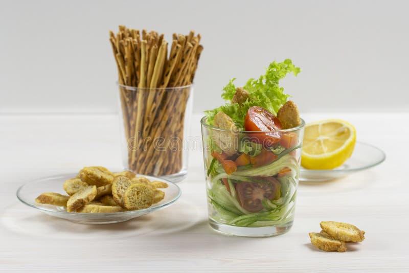 Frischgemüsesalat in einem transparenten Glas auf Weiß Kirschtomaten-Gurkenkopfsalatcroutons, Zitronensaftbehandlung salzig stockbild