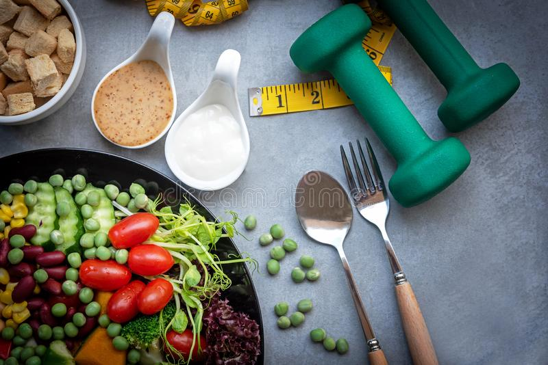 Frischgemüsesalat und gesunde Nahrung für Sportausrüstung für Frauen nähren das Abnehmen mit Maßhahn für Gewichtsverlust auf schw lizenzfreie stockfotografie