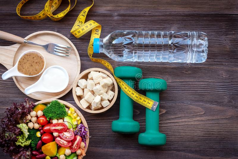 Frischgemüsesalat und gesunde Nahrung für Sportausrüstung für Frauen nähren das Abnehmen mit Maßhahn für Gewichtsverlust lizenzfreie stockfotos