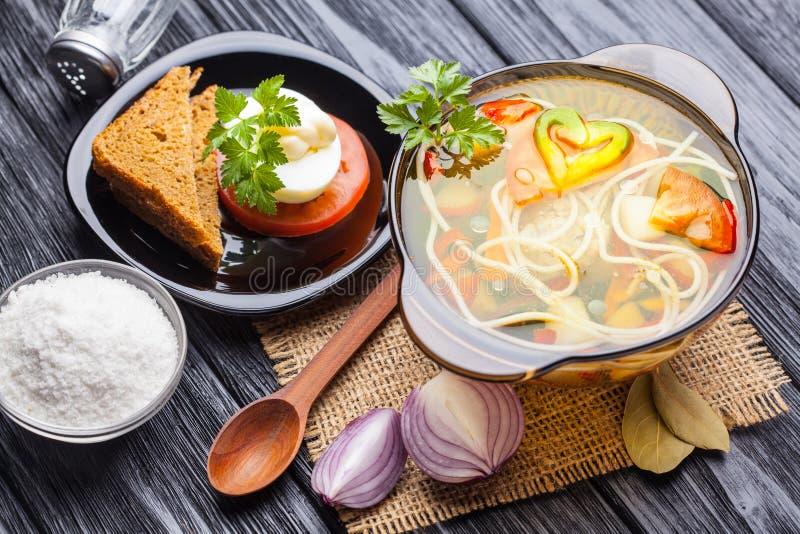 Frischgemüsesuppe mit Nudeln in einem Topf auf Schwarzem stockfotos
