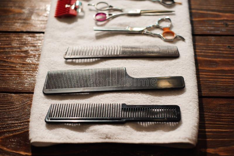 Friseringhjälpmedel på en handduk - sax, hårkammar, clipper royaltyfria bilder