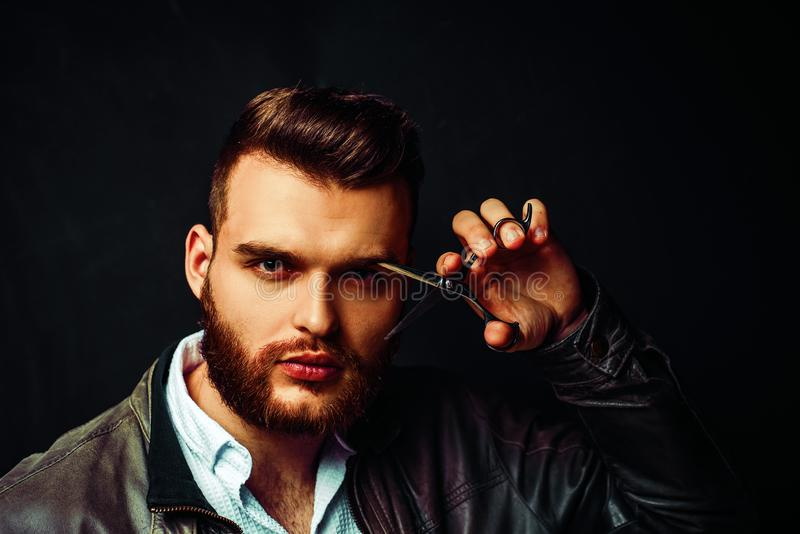 Frisersalongbegrepp Sk?ggig man, sk?ggig man Stående av den stilfulla mannen med skägget Barberaresax och rak rakkniv arkivbilder