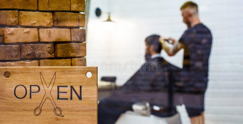 Frisersalongsalong Öppen barder shoppar Frisör eller barberare Mannen som besöker frisören i barberare, shoppar Man med skägget i arkivfoto