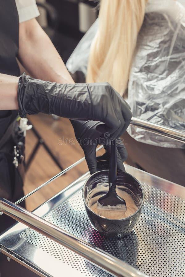 Friseur übergibt das Vorbereiten einer Färbung in einem Behälter lizenzfreie stockbilder