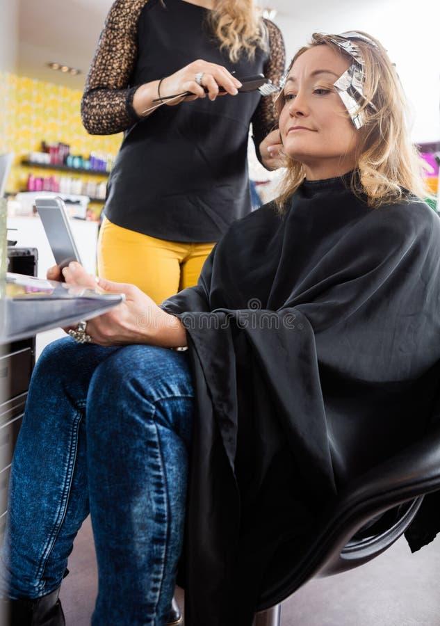 Friseur Applying Hair Dye zur Frau im Salon lizenzfreie stockbilder