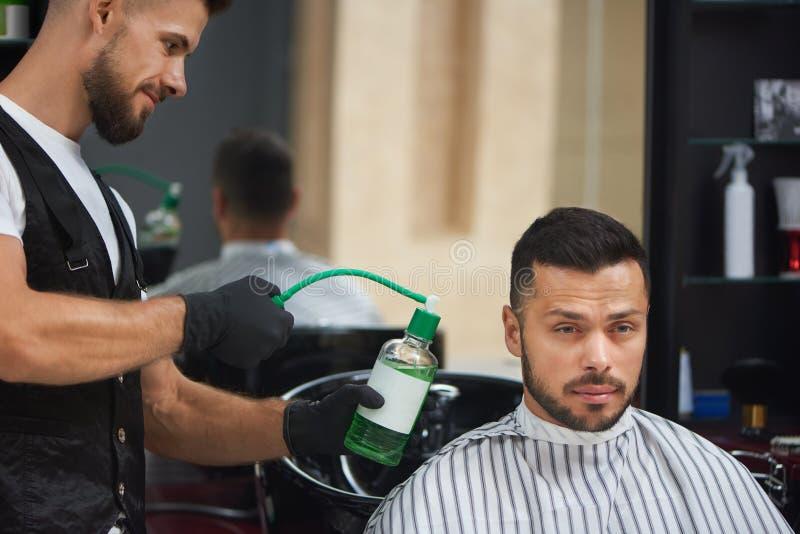 Friseur in den schwarzen Handschuhen grünes Wasser auf gutaussehendem Mann besprühend lizenzfreie stockfotos