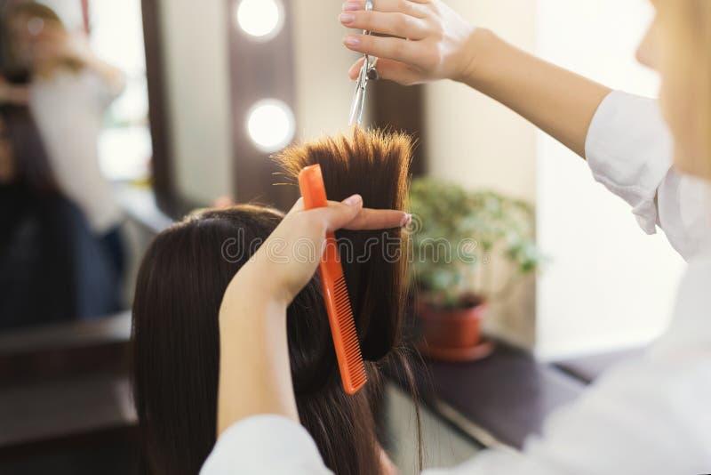 Friseur, der braunes Haar mit Scheren trimmt stockfotografie