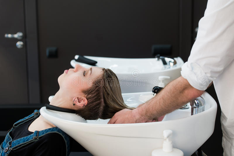 Friseur, der das Haar des jugendlich Mädchens im Schönheitssaal wäscht lizenzfreie stockbilder