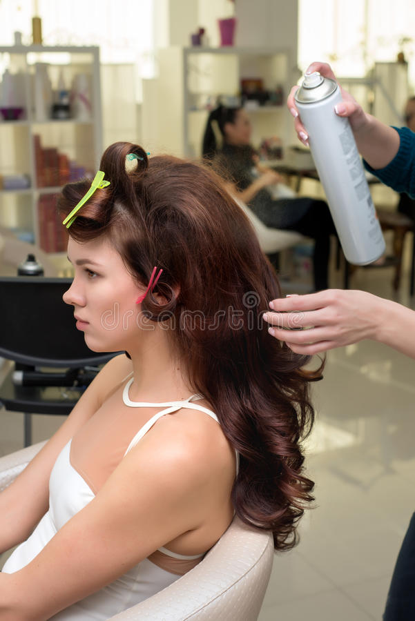 Friseur, der der Brunettefrau Ringellocken macht Friseurarbeit lizenzfreies stockbild