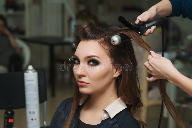 Friseur, der der Brunettefrau Ringellocken macht Friseurarbeit lizenzfreie stockfotografie