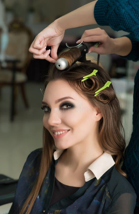 Friseur, der der Brunettefrau Ringellocken macht Friseurarbeit lizenzfreie stockfotos