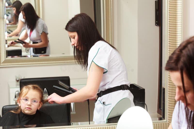 Friseur, der Kind des kleinen Mädchens des Haares im Frisurnschönheitssalon geraderichtet lizenzfreie stockfotografie