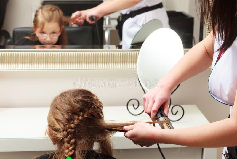 Friseur, der Kind des kleinen Mädchens des Haares im Frisurnschönheitssalon geraderichtet stockbilder