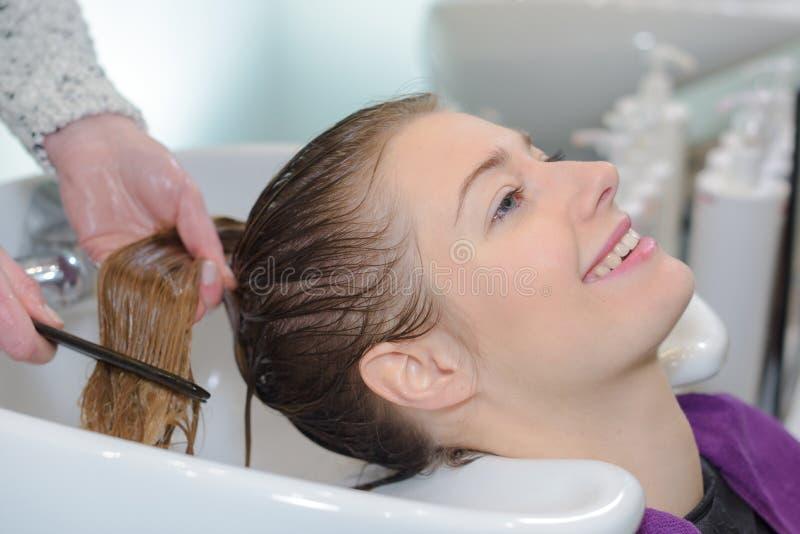 Friseur, der Kunde ` s Haar wäscht und kämmt stockfoto