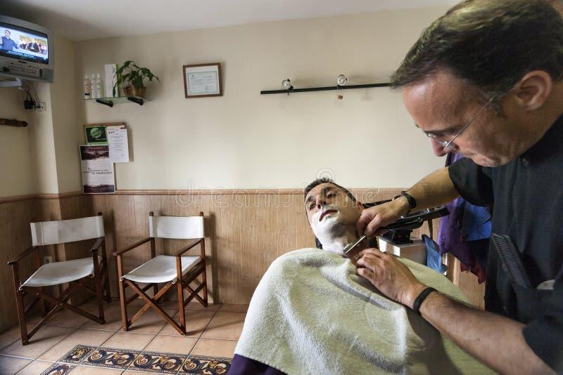 Friseur, der mit einem Rasiermesser zum jungen Mann in einem Shop des Friseurs sich rasiert stockfoto