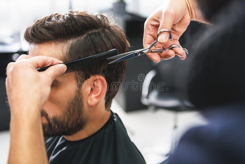 Friseur, der Scheren und Kamm verwendet lizenzfreie stockfotografie