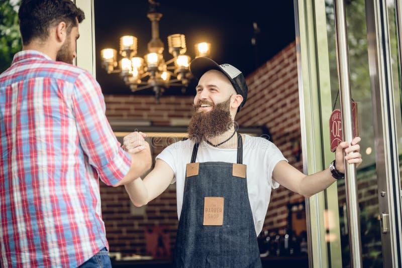 Friseur, der seinen männlichen Kunden am Eingang eines kühlen Friseursalons grüßt stockfotos