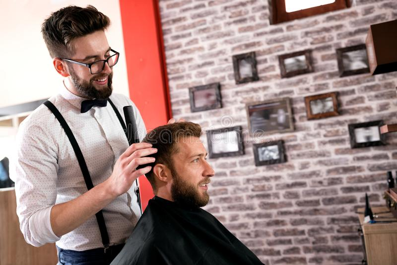 Friseur justiert Haar ein Kunde mit einem Kamm stockbild