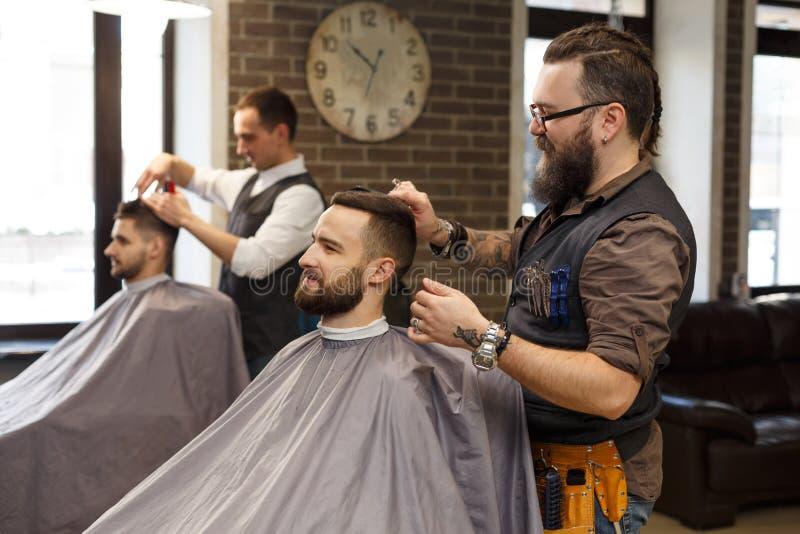 Friseur machen dem Kunden Haarschnitt mit Scheren am Friseursalon stockfoto