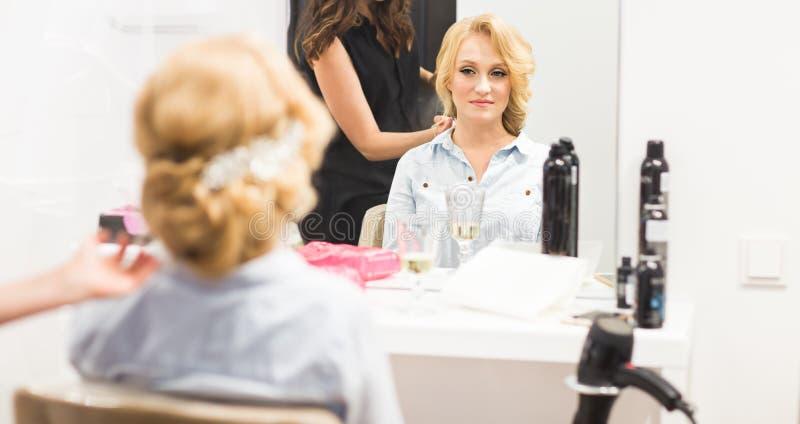 Friseur macht die Braut vor einer Hochzeit stockbild