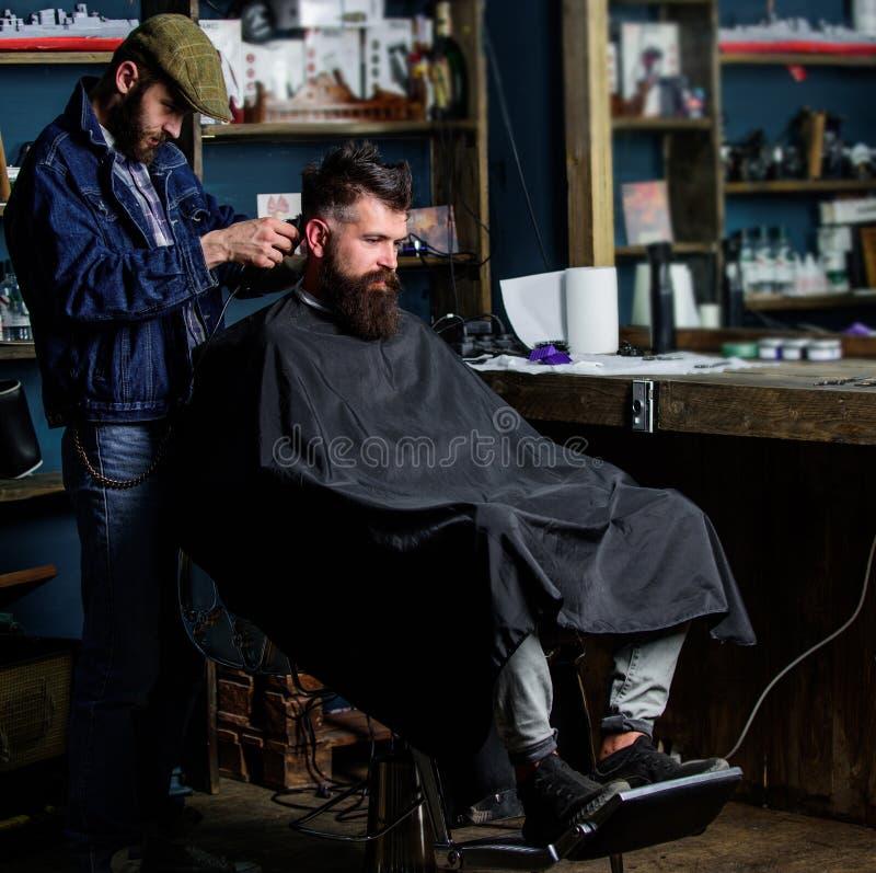 Friseur mit Haarscherer arbeitet an Haarschnitt des bärtigen Kerlfriseursalonhintergrundes Hippie-Kunde, der Haarschnitt erhält h lizenzfreie stockbilder