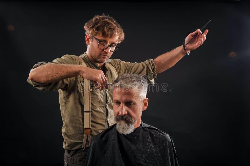 Friseur schneidet älteren Bürger mit einem Bart auf dunklem Hintergrund stockbild