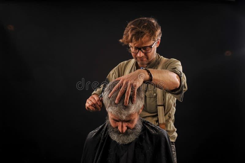 Friseur schneidet älteren Bürger mit einem Bart auf einem dunklen Hintergrund stockfoto