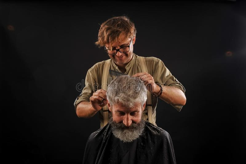 Friseur schneidet älteren Bürger mit einem Bart auf einem dunklen Hintergrund stockbilder