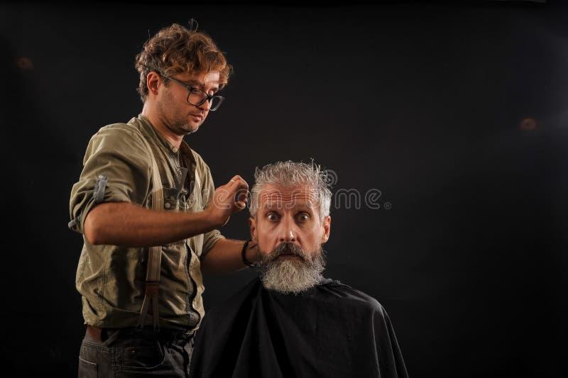 Friseur schneidet älteren Bürger mit einem Bart auf einem dunklen Hintergrund lizenzfreies stockbild