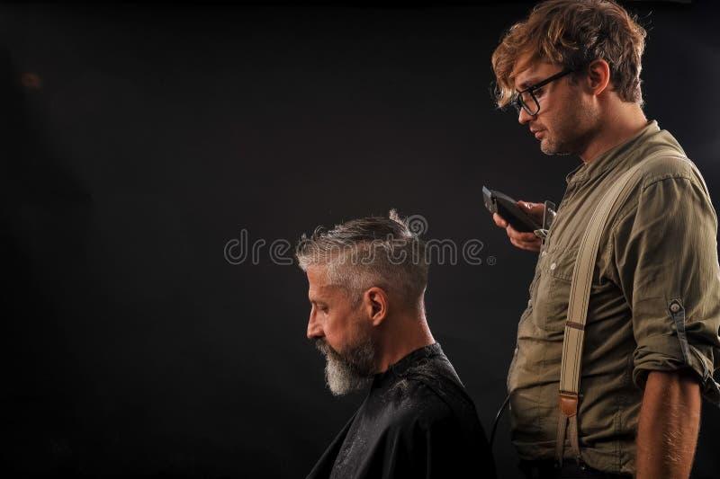 Friseur schneidet älteren Bürger mit einem Bart auf einem dunklen Hintergrund lizenzfreies stockfoto