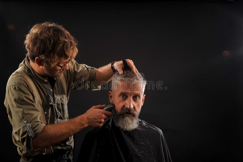 Friseur schneidet älteren Bürger mit einem Bart auf einem dunklen Hintergrund lizenzfreie stockfotos