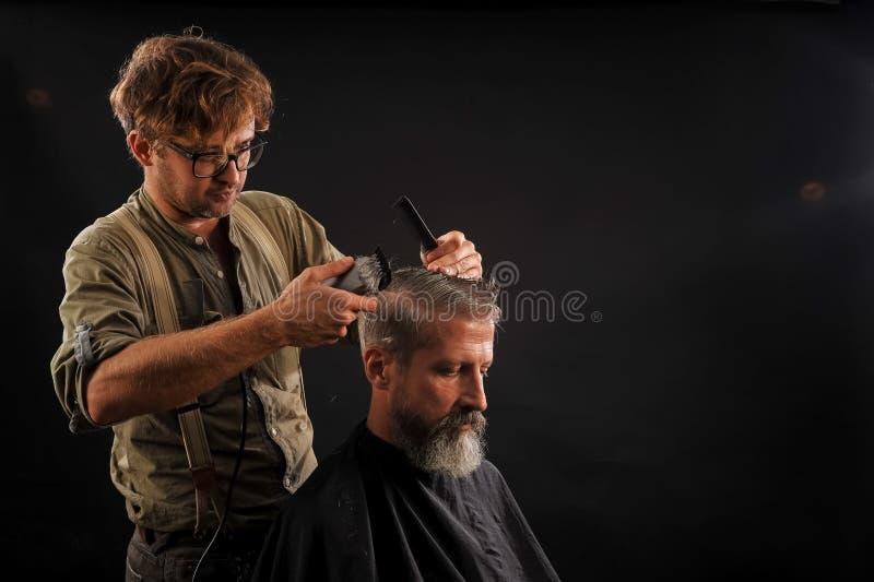 Friseur schneidet älteren Bürger mit einem Bart auf einem dunklen Hintergrund stockfotos