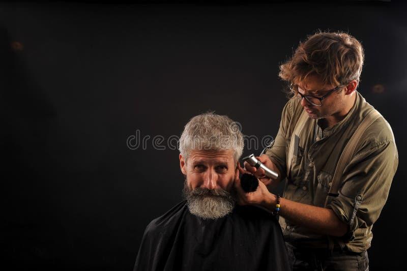Friseur schneidet älteren Bürger mit einem Bart auf einem dunklen Hintergrund stockbild