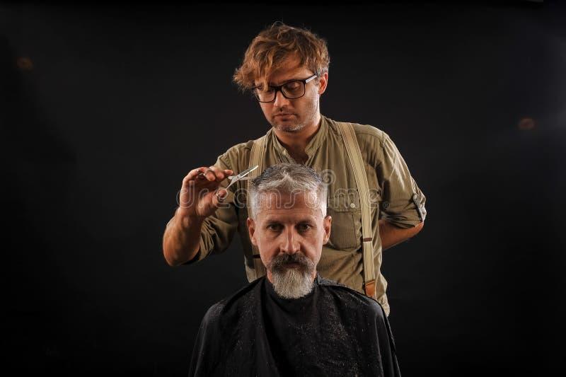 Friseur schneidet älteren Bürger mit einem Bart auf einem dunklen Hintergrund stockfotografie