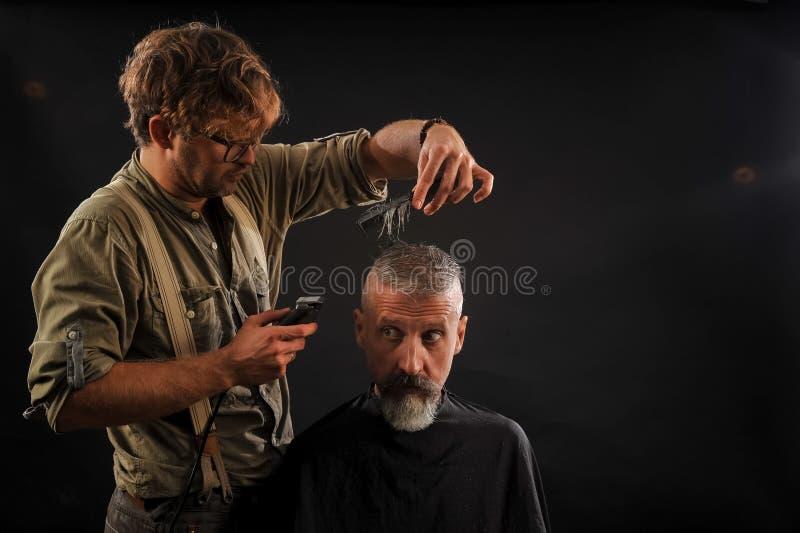 Friseur schneidet älteren Bürger mit einem Bart auf einem dunklen Hintergrund lizenzfreie stockfotografie