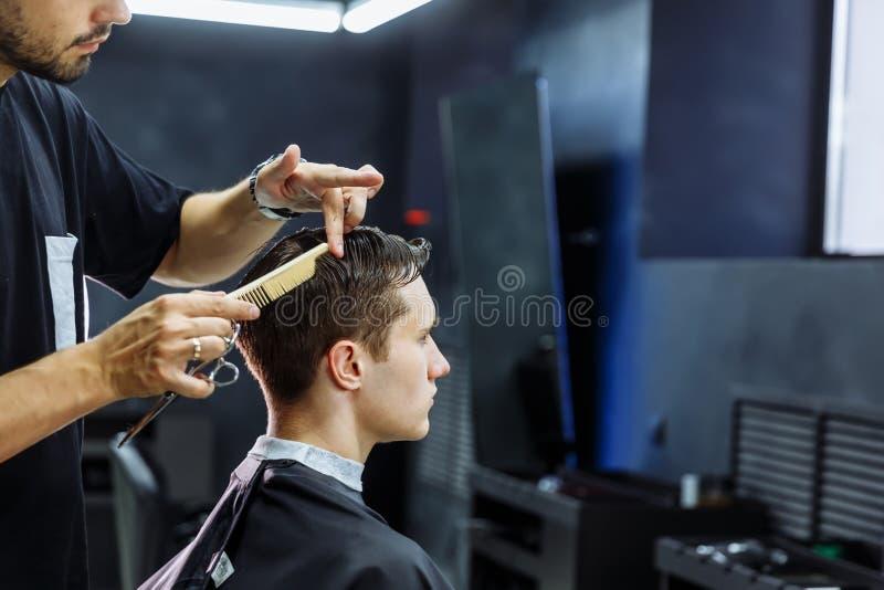 Friseur schneidet das Haar des Kunden mit Scheren Abschluss oben Attraktiver Mann erhält einen modernen Haarschnitt im Friseursal stockbild