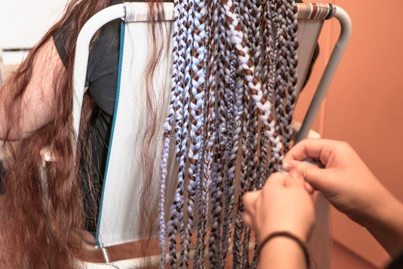 Friseur spinnt Borten mit kanekalon Material zum Kopf des jungen Mädchens, zu den starken Zöpfen oder zu den Zöpfen - Afrikaner-  lizenzfreie stockbilder