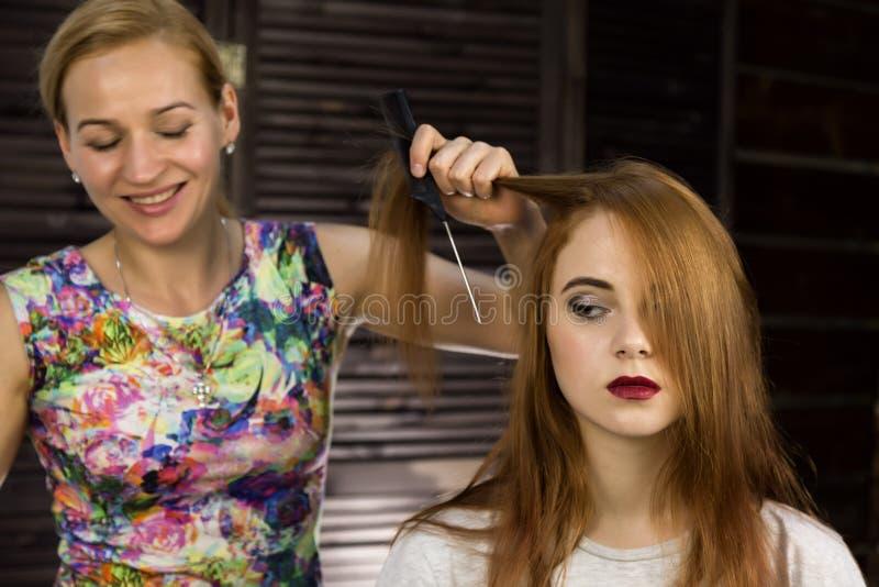 Friseur tut Frisur, damit junge Frau Borten spinnt Konzeptschönheit und -Hochzeit stockfotos