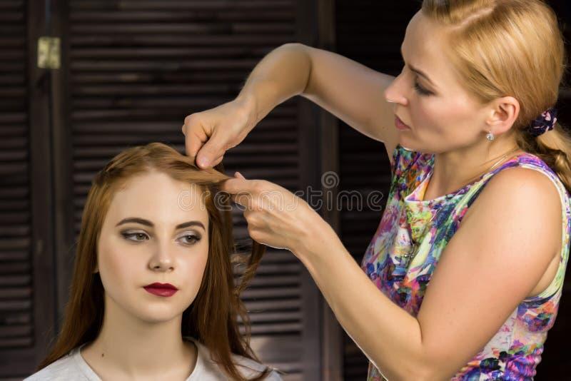 Friseur tut Frisur, damit junge Frau Borten spinnt Konzeptschönheit und -Hochzeit lizenzfreie stockbilder