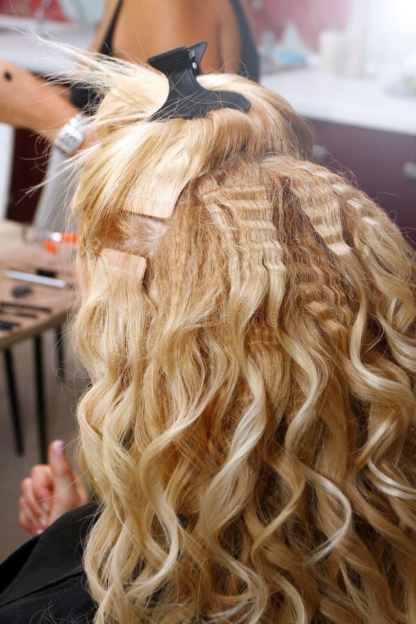 Friseur und Make-upstilist machen Frisur und Make-up von der Braut im Schönheitssalon Herrenfriseur kräuselt Haar blonden g lizenzfreies stockbild