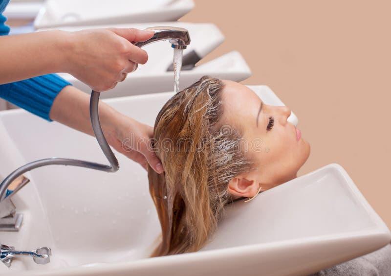 Friseur wäscht das Shampoo weg vom Haar zu einem jungen blonden Mädchen, in einem Schönheitssalon stockfotografie