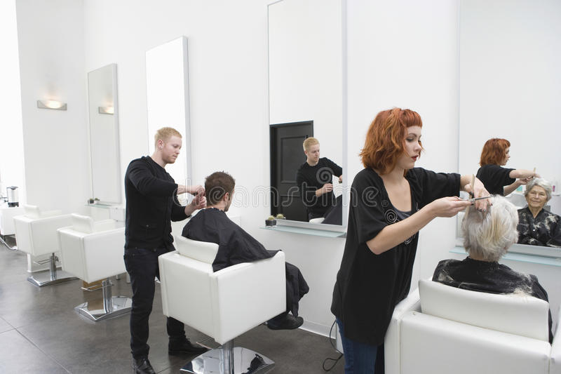 Friseure, die den Kunden Haarschnitt geben stockfotografie