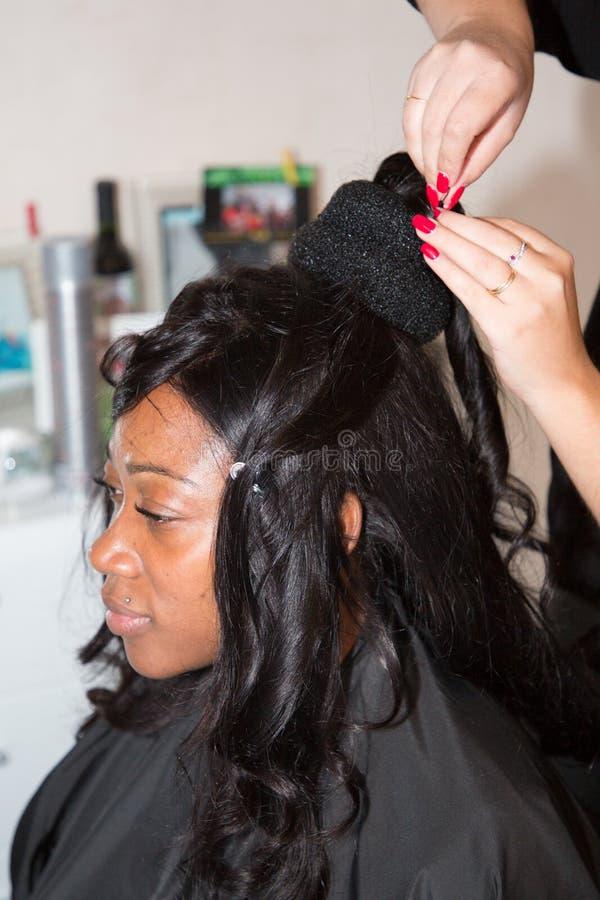 Friseurkünstler Heiratsfrisur zum Bezaubern der amerikanischen schwarzen Brautfrau am Hochzeitstag machen stockfotos