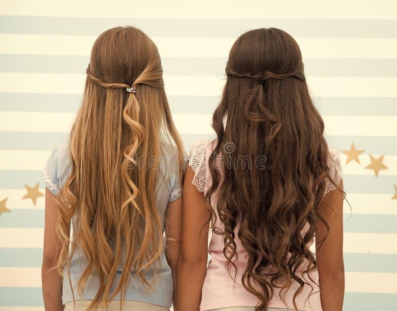 Friseursalondienstleistungen zwei Kinder der kleinen M?dchen mit dem langen Haar am Friseur kleine M?dchen mit dem langen gelockt stockfoto