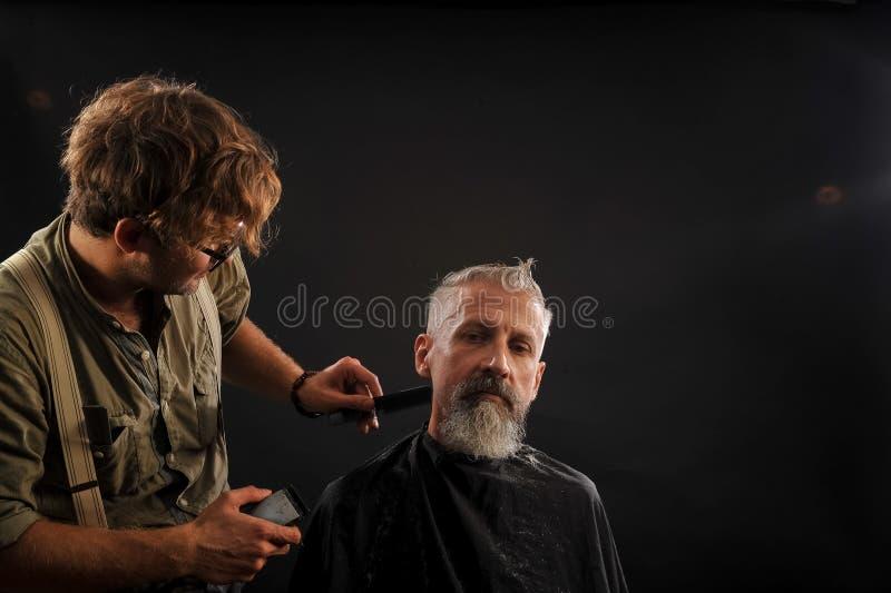 Friseurschnitte ein Bart zu einem Kunden zu einem älteren grauhaarigen lizenzfreies stockfoto