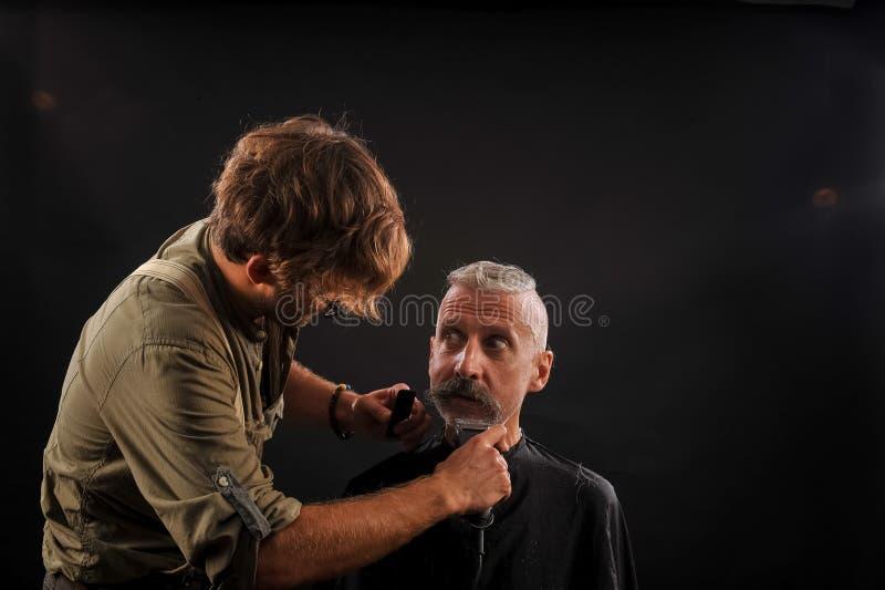 Friseurschnitte ein Bart zu einem Kunden zu einem älteren grauhaarigen Mann stockbild