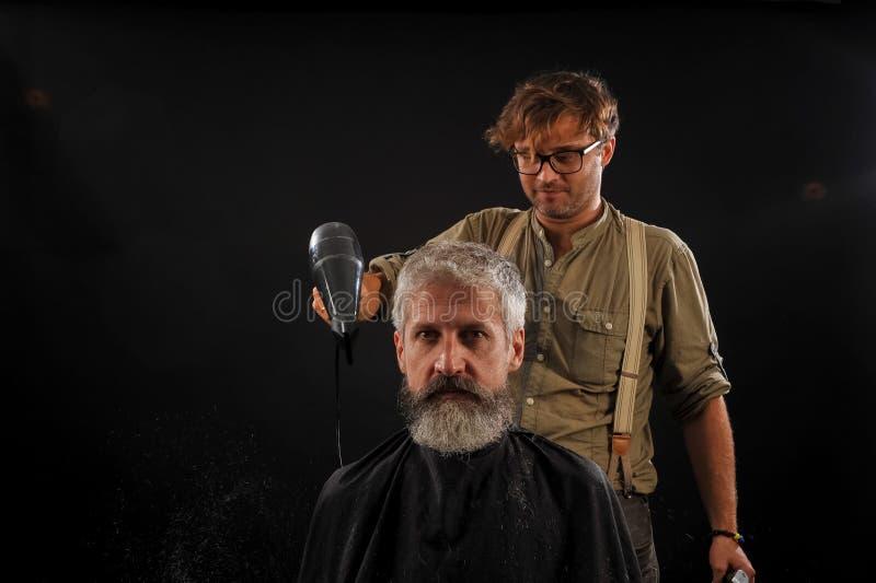 Friseurschnitte ein Bart zu einem Kunden zu einem älteren grauhaarigen stockfotografie