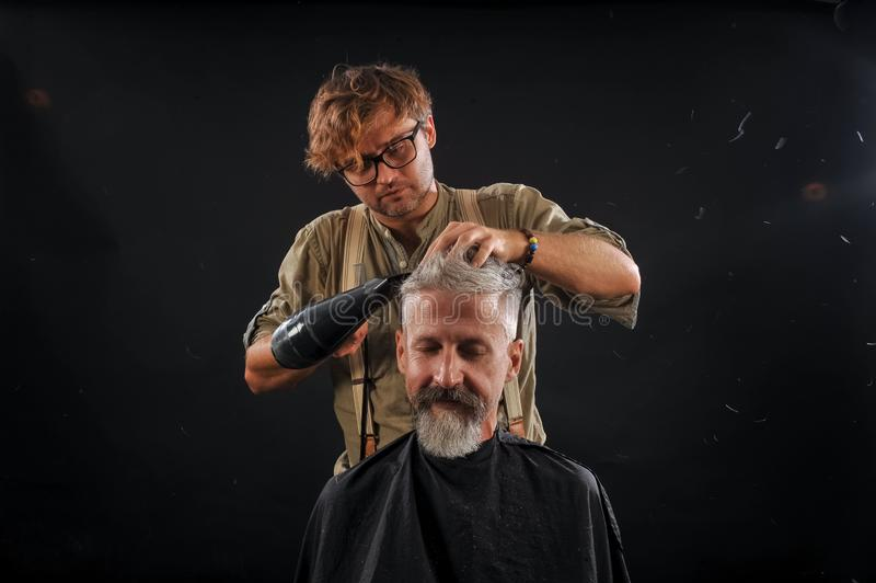 Friseurschnitte ein Bart zu einem Kunden zu einem älteren grauhaarigen lizenzfreie stockbilder