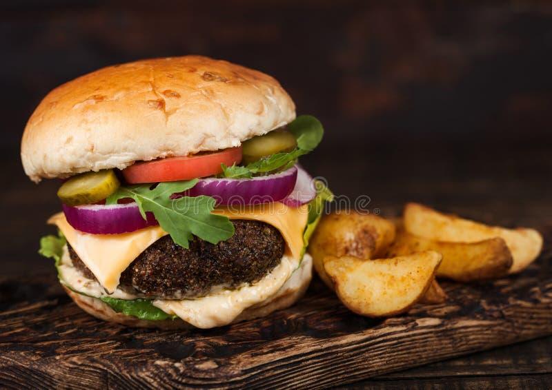 Frisfrischer Bio-Rindfleischburger mit Käse- und Saucen mit Gemüse- und Kartoffelvecken auf Holzbrett stockfotografie
