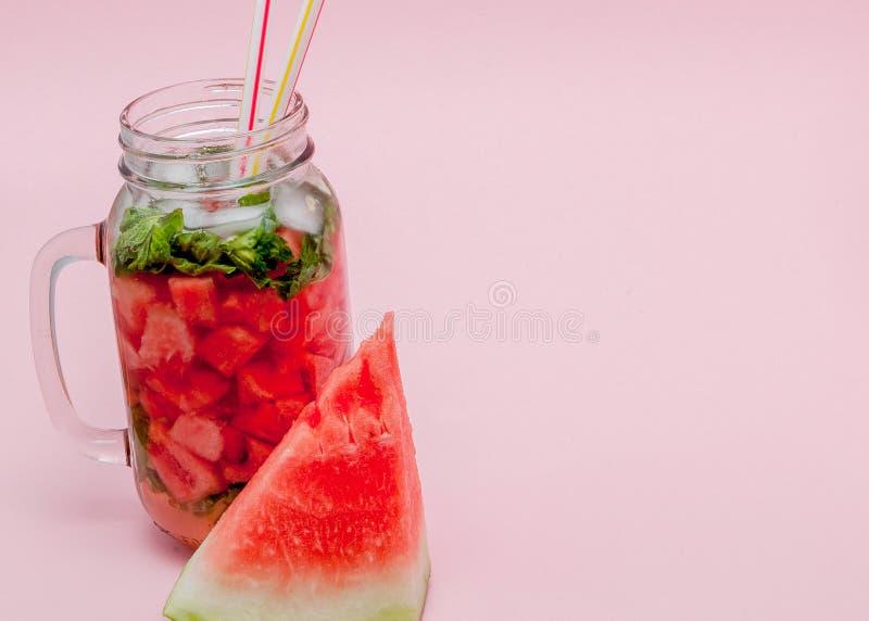 Friskhetvattenmeloncoctail med skivan av frukt och bladet av mintkaramellen på rosa bakgrund, kopieringsutrymme, slut upp arkivbild